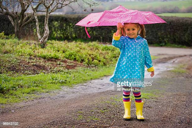 colorfully dressed girl in rain - raincoat stock pictures, royalty-free photos & images