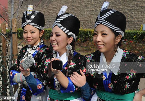 Colorfully dressed Hmong girls take photos of the casket containing Hmong war hero and community leader General Vang Pao during the start of his five...