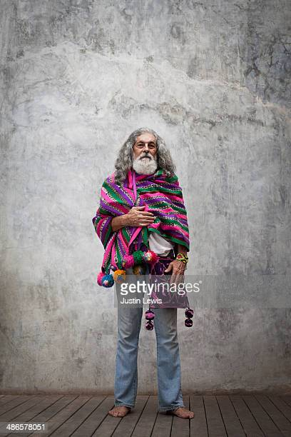 Colorfully dressed older man standing solo