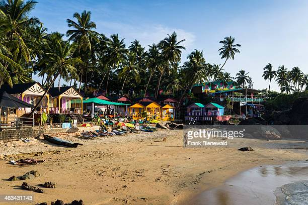 Colorfully painted huts at Palolem Beach with blue sky palm trees and white sand