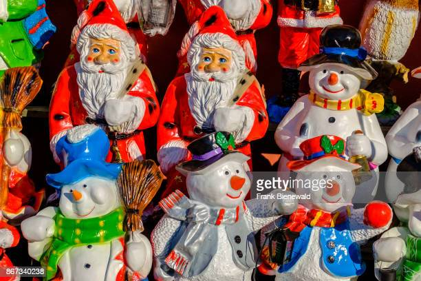 Colorfully painted little statues of Santa Claus and snowman made from clay