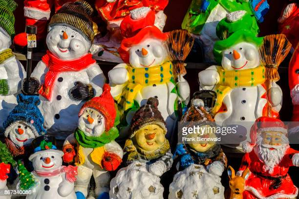 Colorfully painted little statues of snowman made from clay