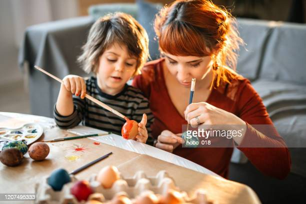 coloring eggs for easter celebration - tempera painting stock pictures, royalty-free photos & images