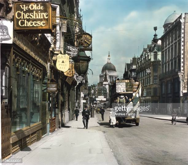 Colorized photo of a view along Fleet Street, looking towards Saint Paul's Cathedral, London, England, 1919. As pedestrians walk past various...