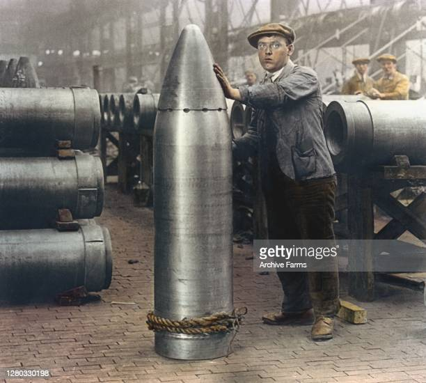 Colorized photo of a worker standing next to a large shell in a munitions factory, England, 1918.