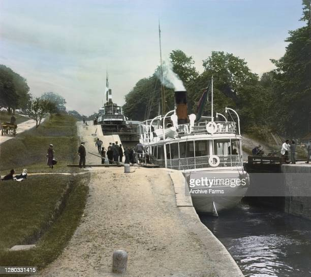 Colorized photo of passengers boarding a steamboat on the Trollhatte Canal at the entrance to the locks, Trollhattan, Sweden, 1902. The boat is named...