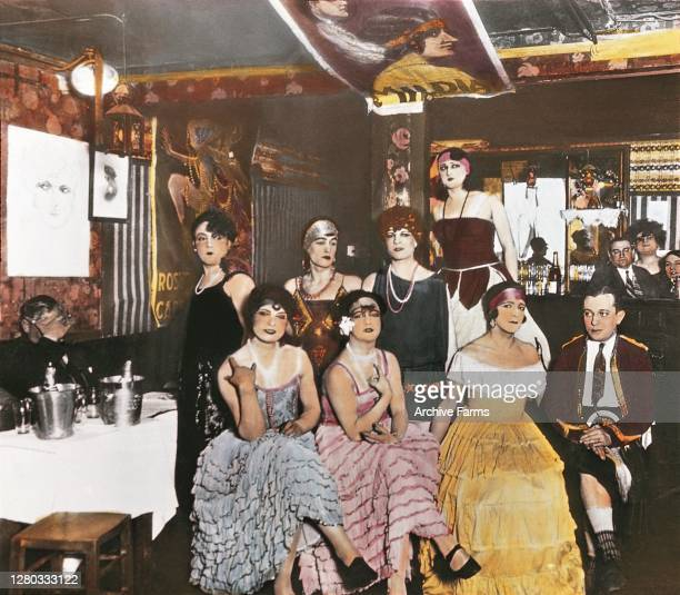 Colorized photo of patrons a number of whom wear elaborate evening gowns in a bar in Montmartre Paris France 1927 The original caption contains a...