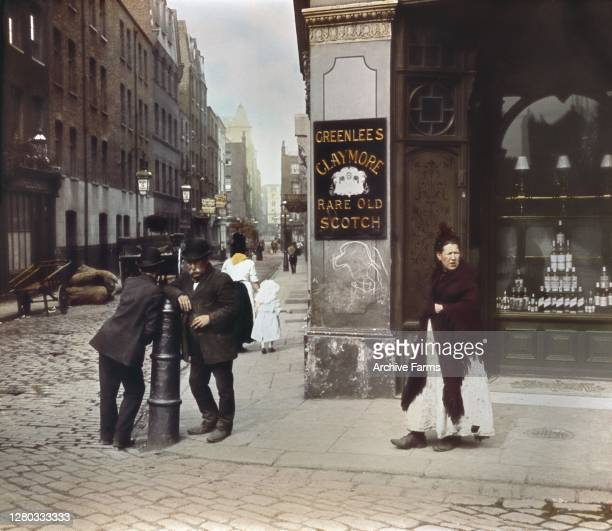 Colorized photo, outside an East End pub, of two men as they lean against a post on the street corner and woman who stands on the sidewalk nearby,...