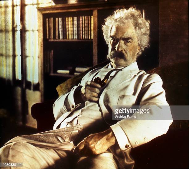 Colorized portrait of American author and humorist Mark Twain, born Samuel Langhorne Clemens holding a pipe and glasses, with a newspaper in his lap,...