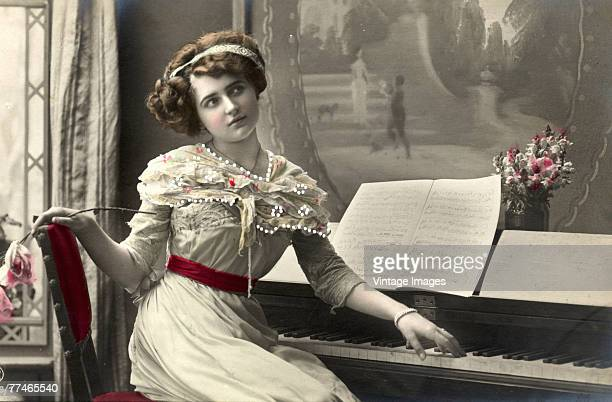 A colorized portrait of an unidentifed young woman as she sits at a piano and gazes wistfully a rose in one hand and the other on the keyboard late...
