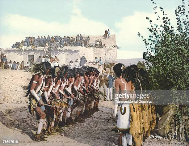 Colorized postcard entitled 'Antelope Priests Chanting At Kisi Moki Snake Dance' shows a group of Native American dancers from the Hopi tribe as they...