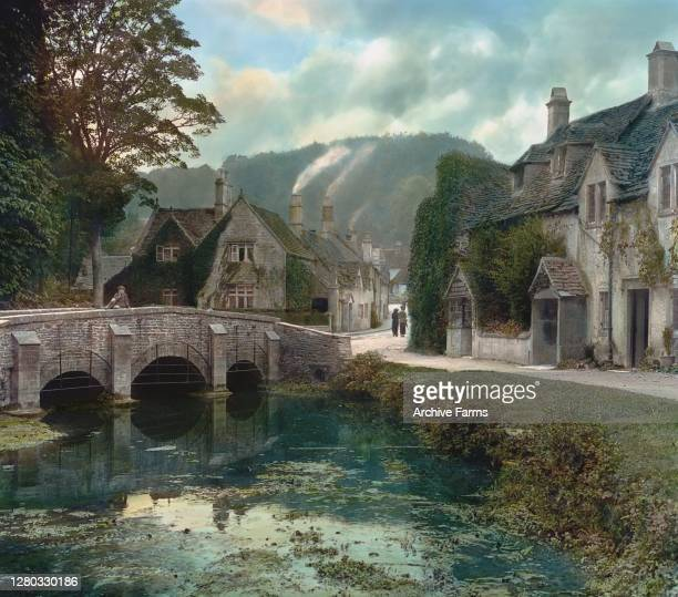 Colorized view of a stone bridge over the River Bybrook which leads to the village, Castle Combe, Wiltshire, England, 1914.