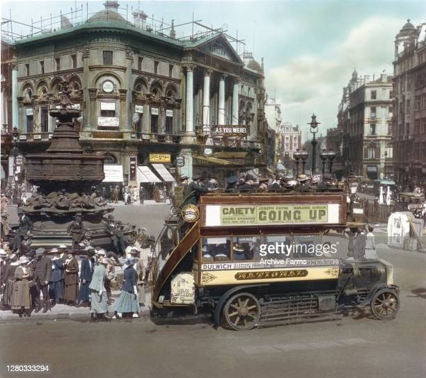Colorized view of a street scene in Piccadilly Circus, London, England, 1919. Passengers board a double decker bus next to the Shaftesbury Memorial...