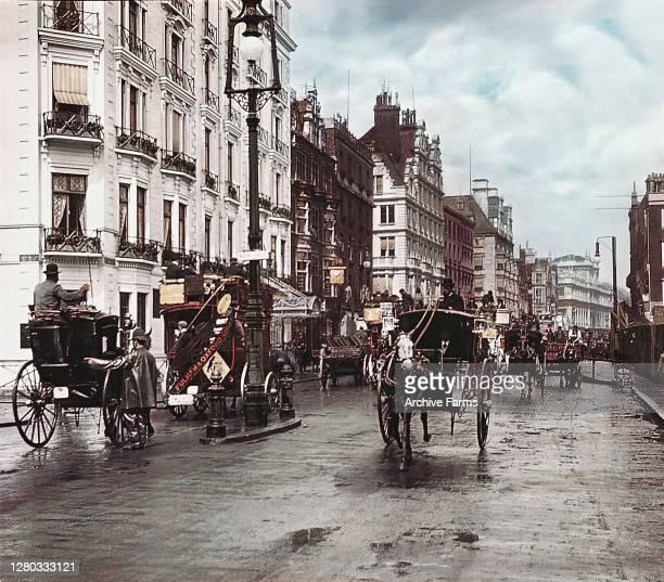 Colorized view of horse-drawn carriages traveling in both directions on Oxford Street, London, England, 1897. A policeman, visible at left, stands in...