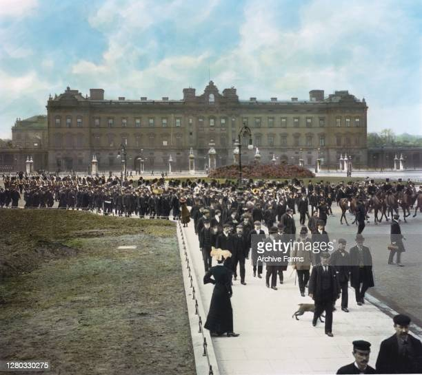 Colorized view of onlookers as they accompany the military parade, known as Trooping the Colour, departing from Buckingham Palace , London, England,...