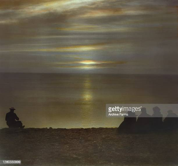Colorized view of people in silhouette as they watch the 'midnight sun' from the North Cape, Mageroya, Norway, 1909.