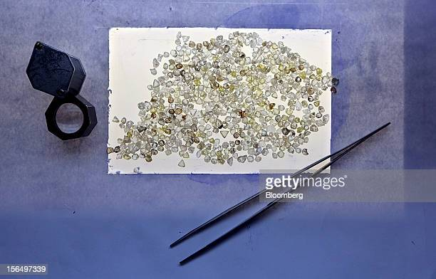 Colorless and colored uncut diamonds sit beside tweezers and a magnifying glass at a sorting table at DTC Botswana a unit of De Beers in Gaborone...