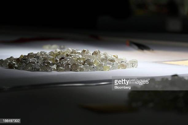 Colorless and colored uncut diamonds sit on a sorting table during the grading process at DTC Botswana a unit of De Beers in Gaborone Botswana on...