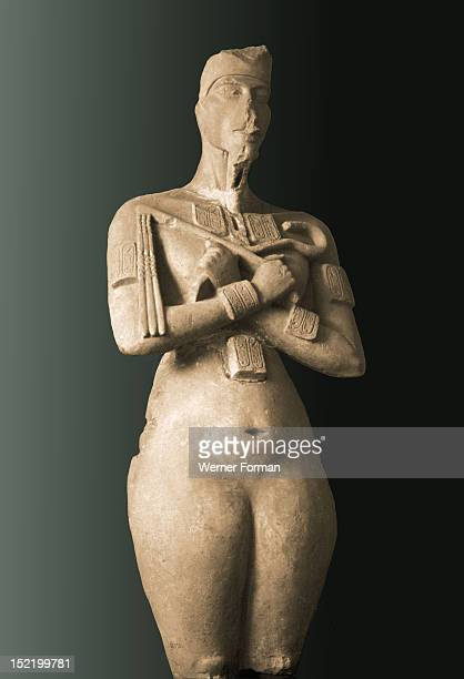 Colossal statue of Akhenaten standing with arms folded holding the flail and heka scepters The lack of genitalia is thought to be a reflection of the...