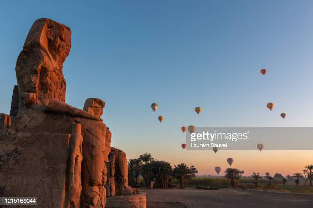 colossi of memnon at dawn with hot air balloons in the sky, luxor, nile valley, egypt - laurent sauvel photos et images de collection