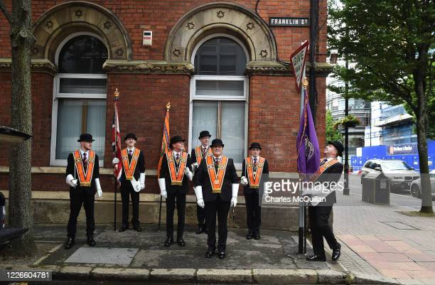 Colour party of Orangemen pose for a group photograph as they make their way to a wreath laying ceremony at Belfast City Hall on July 13, 2020 in...