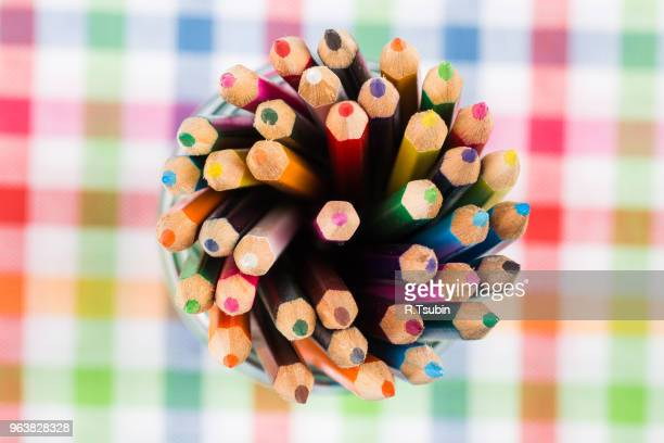 Colour pencils in the glass over colorful background