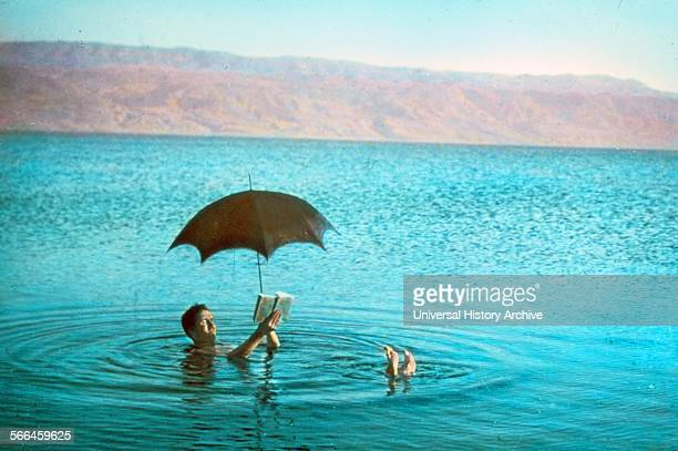 Colour photograph of a man floating in the Dead Sea whilst reading a book and holding an umbrella Dated 1930