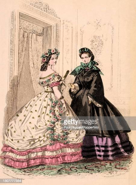 Colour plate from the Englishwoman's Domestic Magazine, showing two young women in a drawing room, one wears a low cut evening gown in white floral...