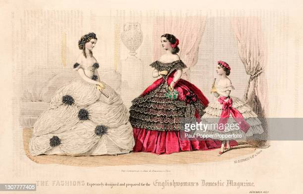 Colour plate from the Englishwoman's Domestic Magazine, showing two young women and a girl in evening gowns, one wears an off the shoulder white...