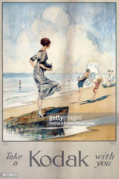 Colour poster produced for Kodak Ltd showing the 'Kodak Girl' standing on a rock on a beach holding a small camera The introduction of portable...