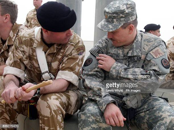 Colour Sgt Paul Annett of the Royal Marines band talks about the American Flag on the uniform of US Major Philip Martin during the ceremony to hand...