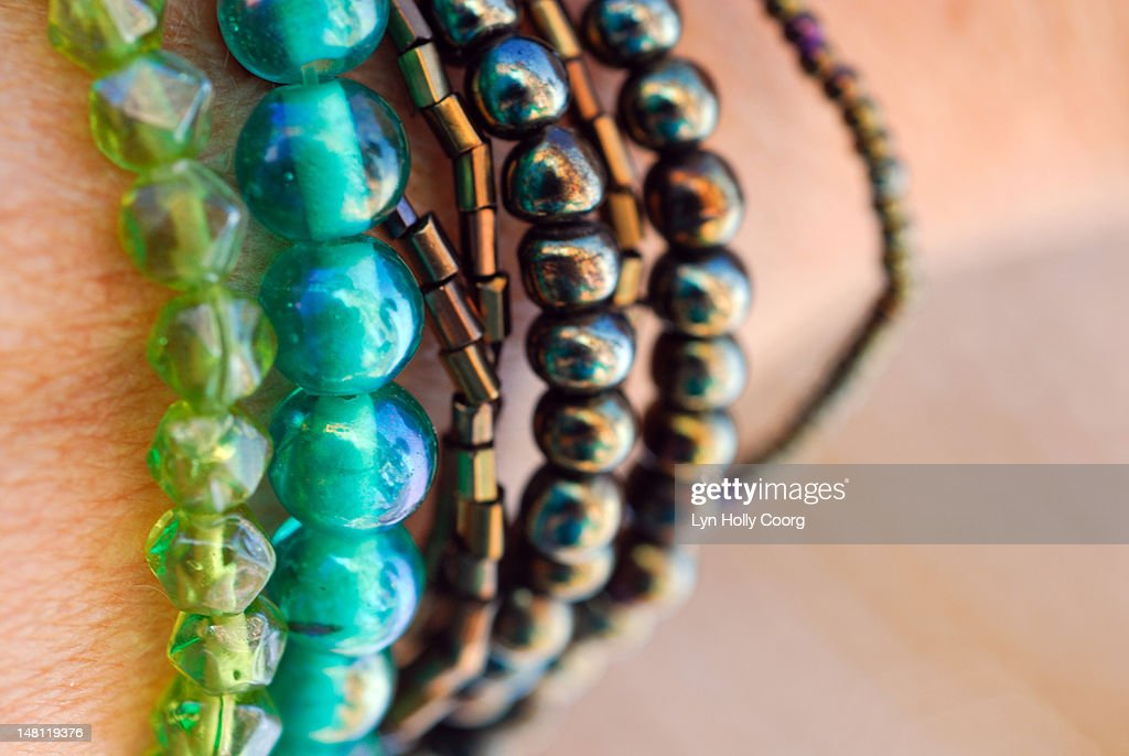Coloured beads on a woman's wrist : Stock Photo