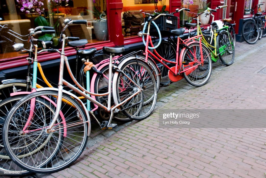 Coloured bicycles parked outside shop : Stock Photo
