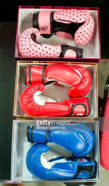 Coloured boxing gloves are seen in boxes as Britain's Prince William Duke of Cambridge and his wife Britain's Catherine Duchess of Cambridge visit...