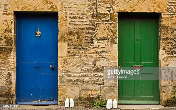 Coloured doors with milk bottles awaiting collection.