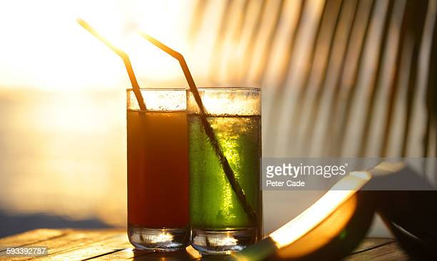 Coloured drinks in glasses against sunset