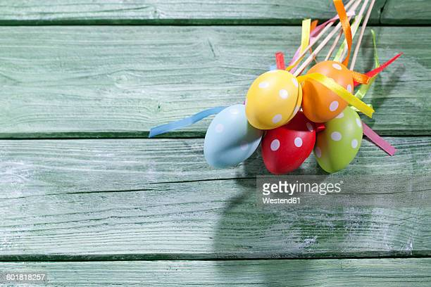Coloured Easter eggs with polka-dots on green wood