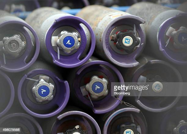 Coloured gas tanks are seen stacked in a storage rack at the Air Liquide SA distribution site in London UK on Friday Nov 20 2015 Air Liquide's $103...