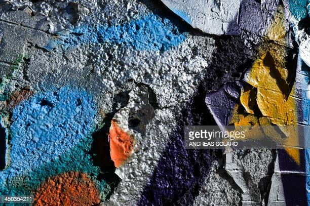 A coloured graffiti is pictured on the wall of the Cultural Centre Ex Mattatoio in Rome on November 17 2013 AFP PHOTO / ANDREAS SOLARO