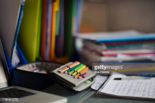 coloured pencils in a pencil case on a desk surrounded by student textbooks, filing trays and homework - pencil case stock pictures, royalty-free photos & images