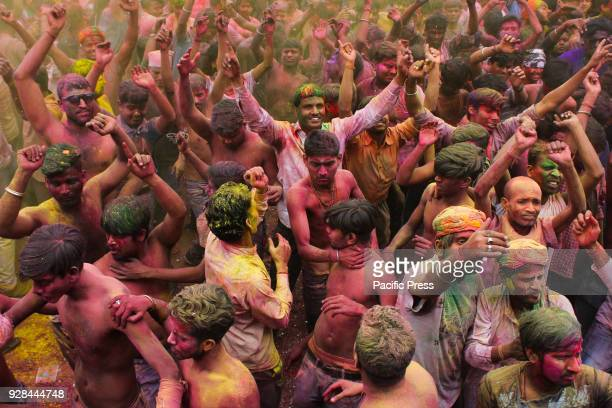 BAZAR GUWAHATI ASSAM INDIA Coloured powder is thrown on men as they dance during Holi celebrations on street