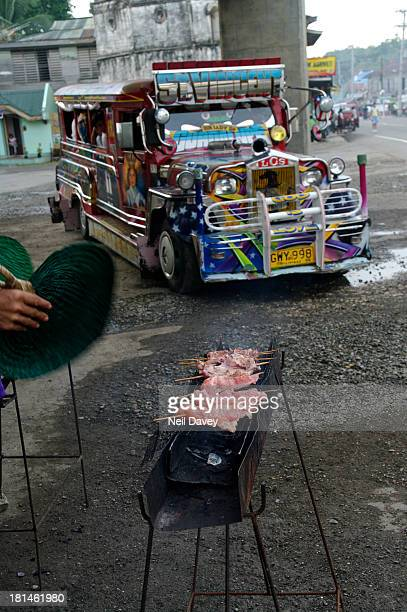 CONTENT] Colourful Americanmade jeepney bus in the streets of Loboc Driving through the central square passed a street vendor grilling meat on a...
