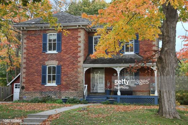 Colourful Autumn leaves on trees by an old house in Unionville, Ontario, Canada.
