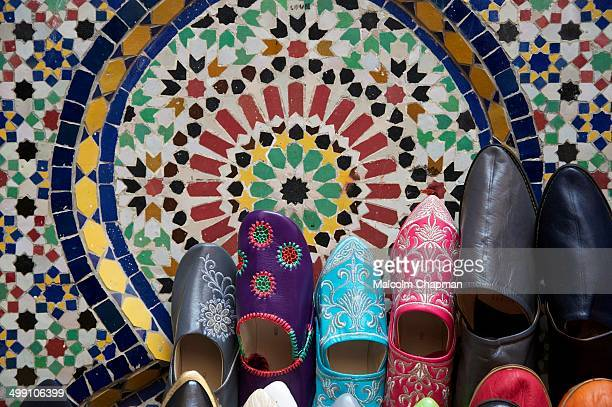 CONTENT] Colourful Balgha babouche slippers on sale in Meknes medina propped up against a Zellige tiled fountain Meknes Morocco