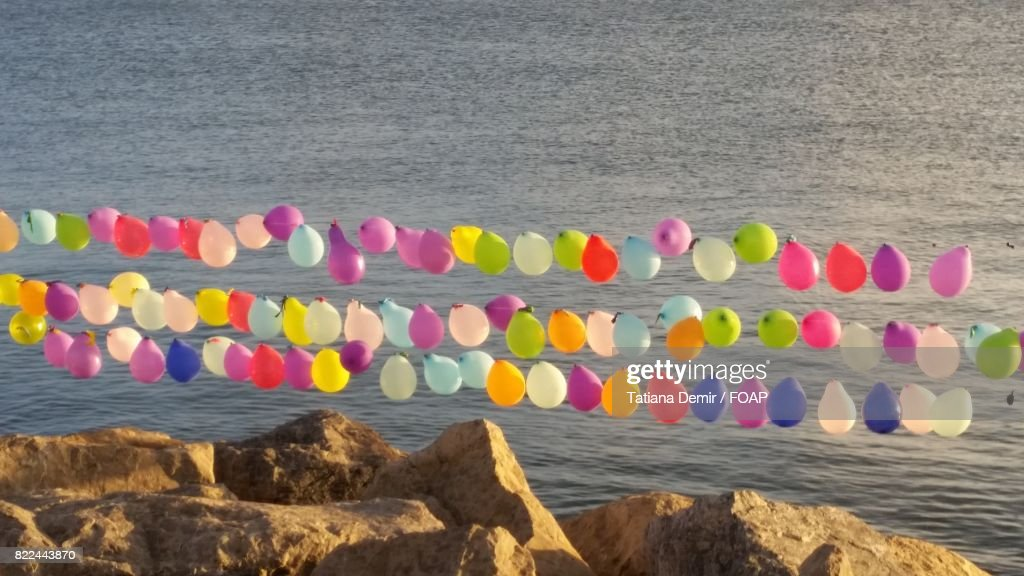Colourful balloons over rock : Stock Photo