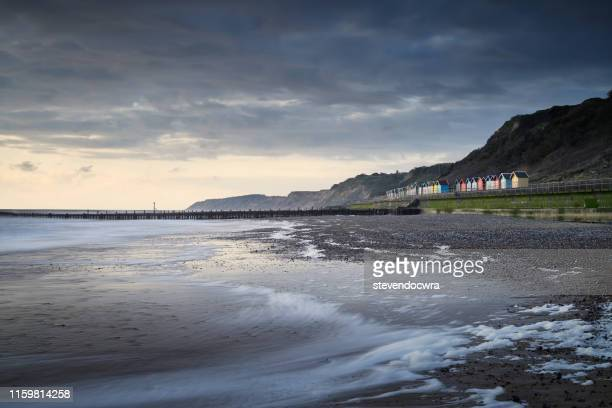 colourful beach huts at overstrand on the norfolk coast illuminated by the dawn sunlight - norfolk east anglia foto e immagini stock