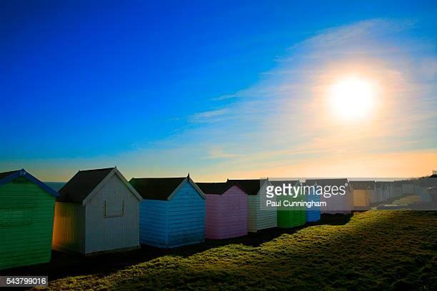 Colourful beach huts bask in the setting sun