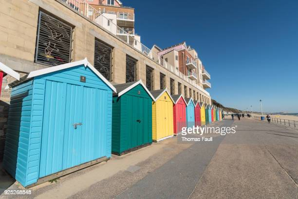 colourful beach huts on boscombe seafront in bournemouth - bournemouth england stock photos and pictures