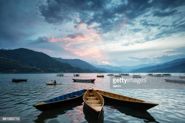Colourful boats on lake in Pokhara with beautiful sunset in background