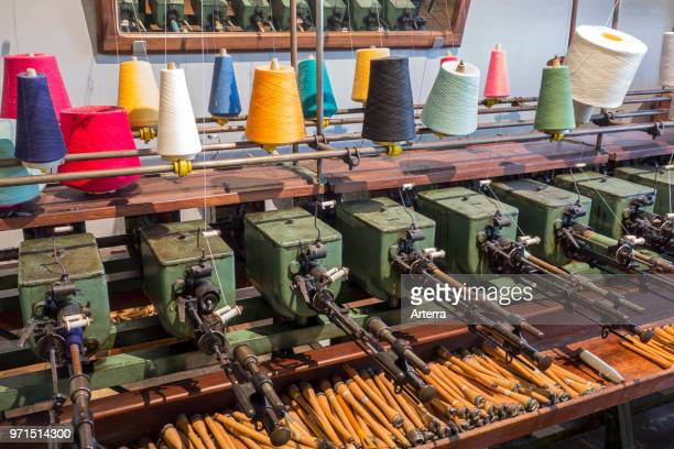 Colourful bobbins with yarns on spool machine in cotton mill / spinningmill